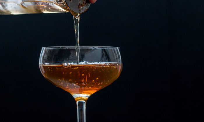 """A simple Manhattan variant, made with 2 parts scotch to 1 part sweet vermouth, with a dash or two of orange bitters.   There is a lot I like about this, but the reflections really annoy me. Time to go back to my copy of """"Light: Science & Magic"""" for a refresher on lighting glass."""